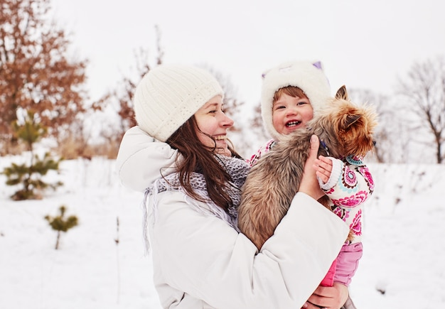 Mom keeps her smiling daughter and little doggy on her hands