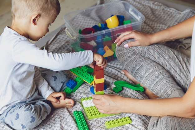 Mom and kid play together in the bedroom on a bed with plastic blocks