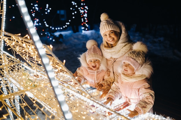 Mom and kids in the evening city with night christmas lights