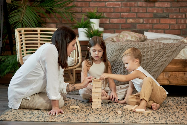 Mom and kids play squirl tower. woman girl and boy play family puzzle game. family day off