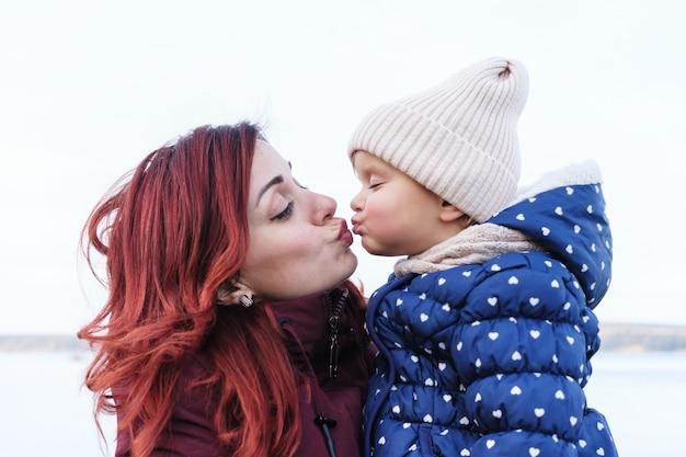 ママは小さな娘にキスします-シングルママは小さな女の子を抱きしめます-幸せなママと娘の関係、唇にキスします-幸せな家族関係の概念