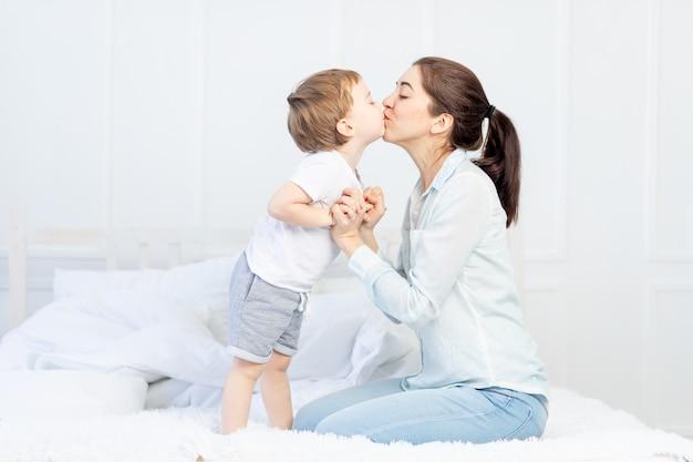 ママはベッドで赤ちゃんにキス、家族と子供たちの概念、母の日