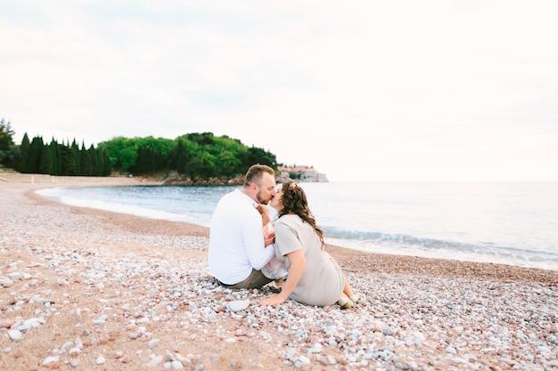 엄마는 빌라 마일로세르 근처 해변에 앉아 있는 동안 팔에 어린 소녀를 안고 아빠에게 키스합니다.