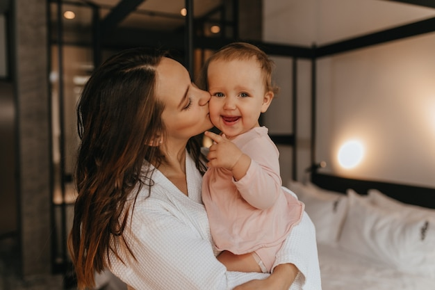 Mom kisses fair-haired child looking at camera with smile. woman holds her daughter in her arms on background of white bed.