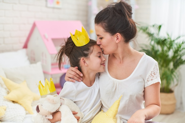 Mom kisses her daughter on the forehead, playing with crowns on the bed