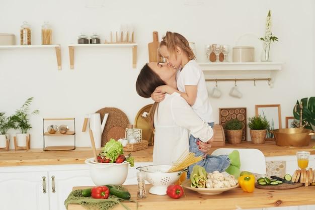 Мама целует дочь на кухне. счастливая семья дома. концепция здорового образа жизни семьи.
