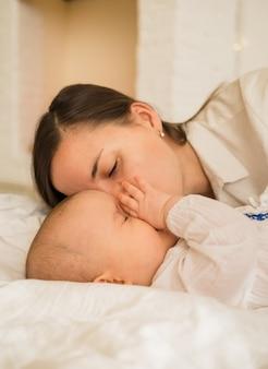 엄마는 침대에 흰 담요에 그녀의 딸을 키스