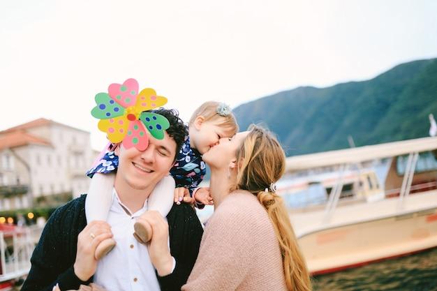 엄마는 딸에게 키스하고 웃는 아빠는 거의 장난감 꽃을 어깨에 짊어지고 있습니다.