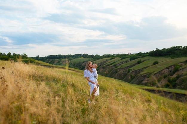 ママは息子にキスします。母の日。母と息子。子供は母親にキスします。子供と一緒に畑にいる女性。こどもの保護の日。人との美しい自然