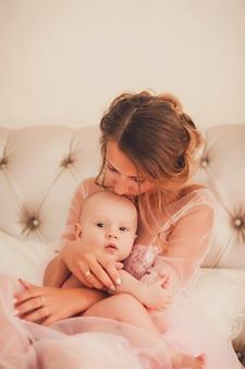 Mom kissing baby boy in bedroom