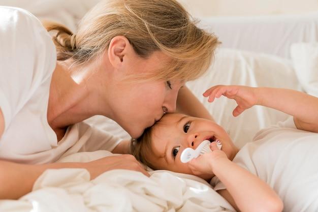 Mamma che bacia bambino sulla fronte