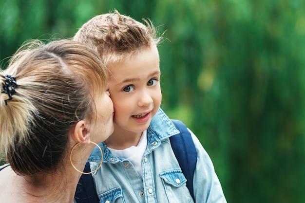 ママは学校に行く前に息子にチェックをキスします。公園でバックパックと青いシャツを着てスタイリッシュな小さな男子生徒
