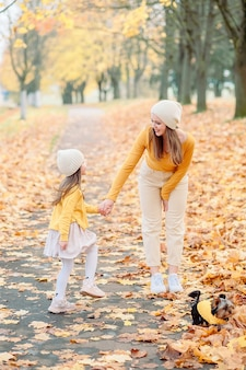 Mom in a knitted hat gently looks at her daughter of five years old holding her hand in the fall against the background of fallen yellow leaves, next to their pet a small dog