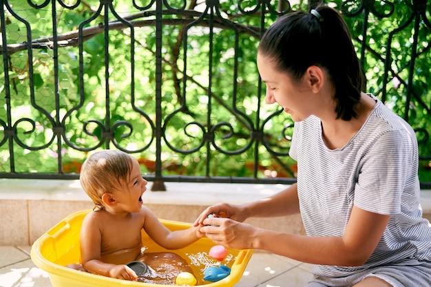 엄마는 발코니에 있는 세면대에서 웃고 있는 어린 소녀에게 거품을 낸다