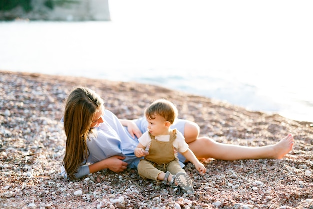 Mom lays with her little son on on the pebble beach near water and plays with him