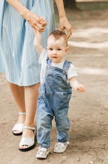 ママは小さな娘の手でリードします。インファンテは歩くことを学ぶ