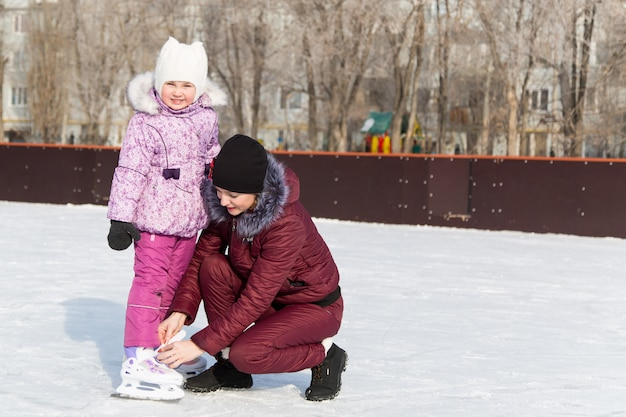 Mom learns a daughter to skate.