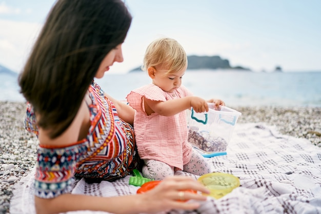 엄마는 앉아 있는 어린 소녀 옆에 자갈 해변에 담요에 누워