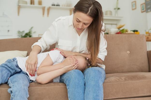 Мама слушает проблемы своей маленькой дочери, обнимает и утешает ее