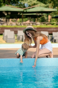A mom and a little boy near the swimming pool