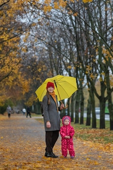Mom and little child are standing under an umbrella in an autumn park. vertical frame.