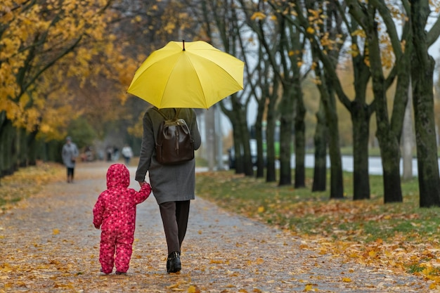 Mom and little child walk under a yellow umbrella in the autumn yellow park holding hands. back view.