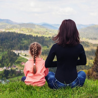 Mom and little daughter are meditating on the top of the mountai