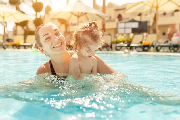 Mom and little daughter are played in the open swimming pool.
