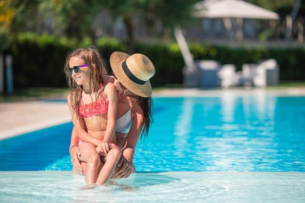 Mom and little daughter enjoying summer vacation in luxury swimming pool