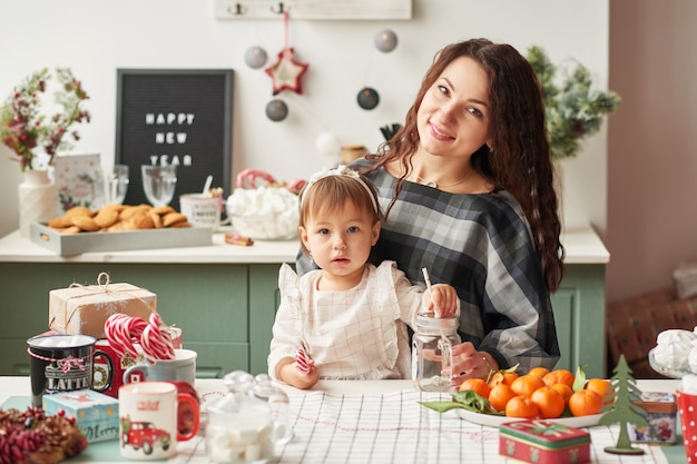 Mom and little daughter in the kitchen decorated for the new year and christmas