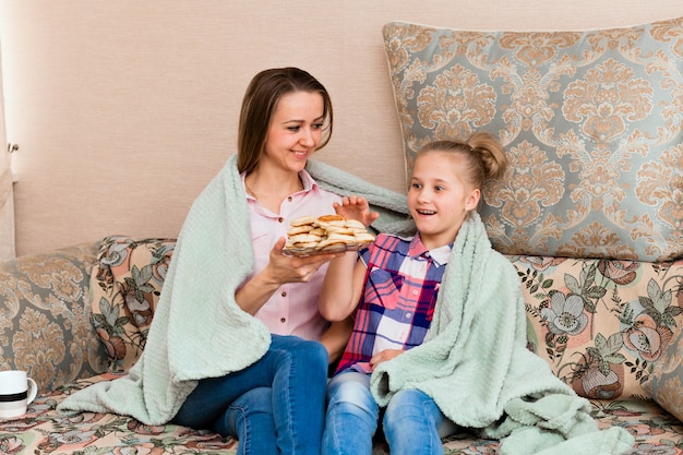 Mom and little girl eat donuts on the sofa in the living room. they are in a good mood, they are smiling at each other.