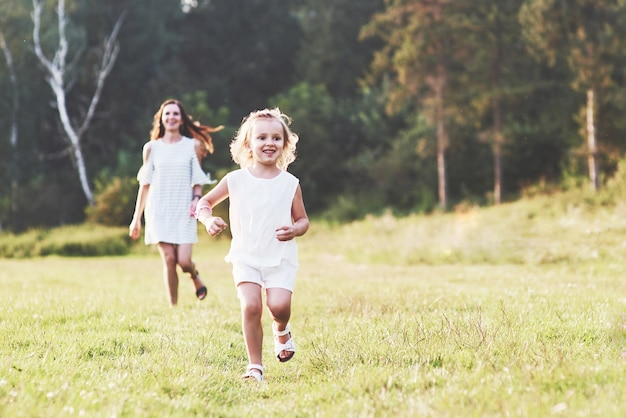 Mom and little girl have walk outside on the field and woods behind