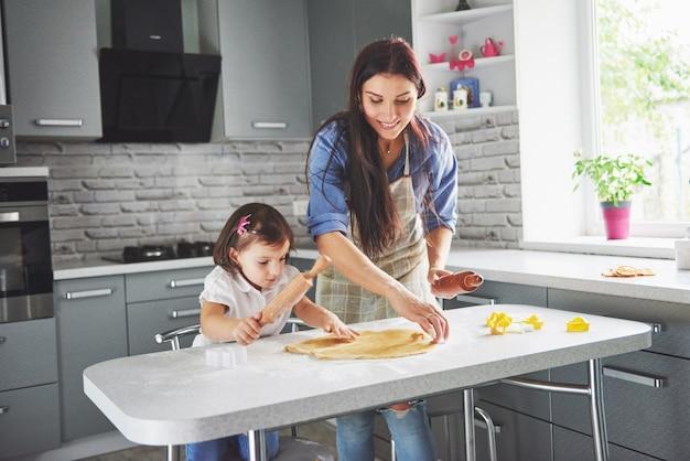 クッキーの娘のためにオーブンを愛するママ。