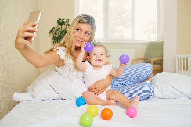 엄마가 방에서 아기와 전화로 사진을 찍습니다.