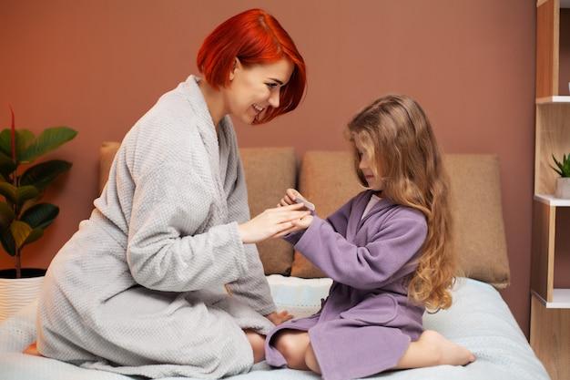 ママは自宅のベッドでマニキュアの娘を作る