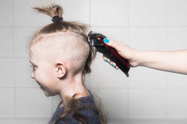 Mom makes a haircut for her son with a clipper. home haircut
