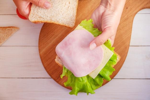 엄마는 학교 아침에 햄과 치즈 샌드위치를 만듭니다.