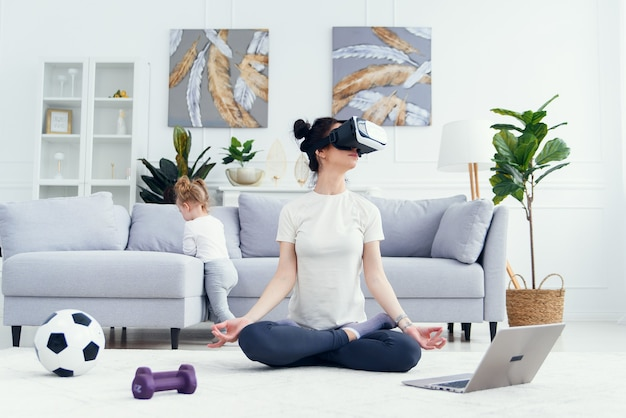 Мама медитирует в позе лотос-йоги с дочерью дома.
