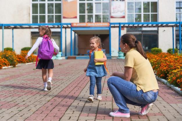 Мама встречает дочь из начальной школы. ребенок на руки бежит своей матери.