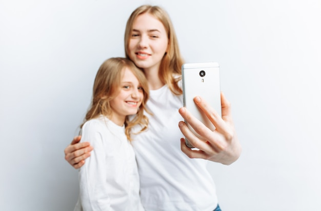 Mom or older sister makes selfie little girl, happy family