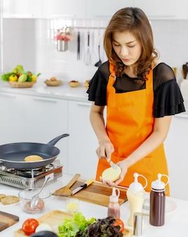 가족 아침 식사를 위해 구운 빵을 준비하는 현대적인 가정 주방에서 날아가는 팬과 가스 스토브 옆에 서 있는 주황색 앞치마를 입은 엄마.