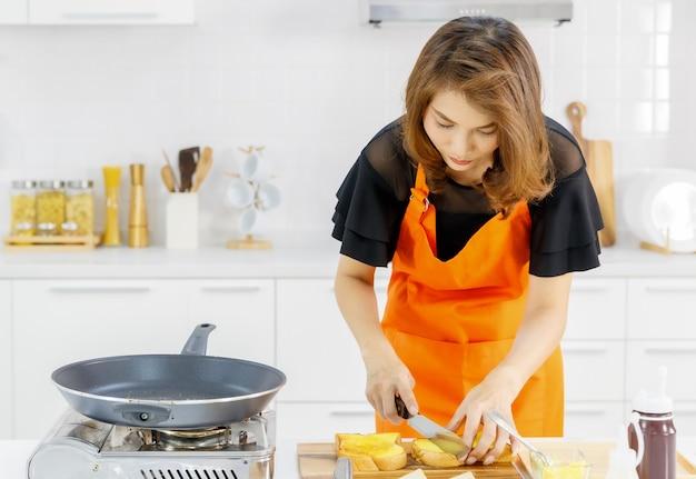 주황색 앞치마를 두른 엄마는 현대적인 가정 주방에서 플라잉 팬과 가스 스토브 옆에 서서 날린 빵을 반으로 잘라 아이들을 위해 맛있는 가족 음식을 요리하는 법을 배웁니다.
