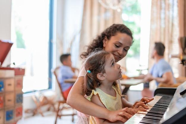 Мама или няня учит маленькую девочку игре на пианино, внимательно наблюдает за движениями пальчиков ребенка и улыбается.