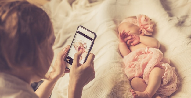 Mom photographs her newborn daughter wrapped in a soft pink blanket