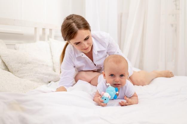 6ヶ月の白いベッドに横たわっている赤ちゃんと遊ぶママ、赤ちゃんと一緒にレジャーママ