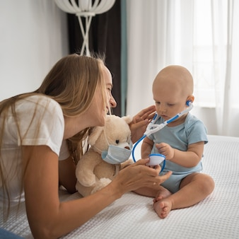 Mom playing with child with teddy bear wearing medical mask