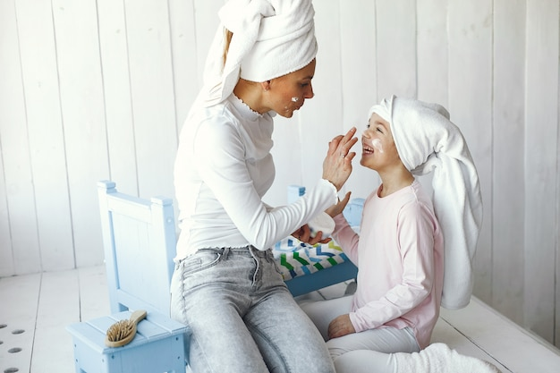 Mom playing with cosmetics with her daughter Free Photo