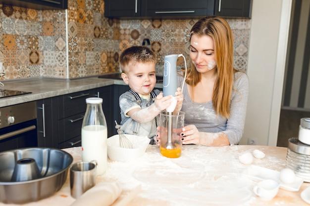 キッチンで子供と遊ぶママ。キッチンは濃い色と素朴なスタイルです。