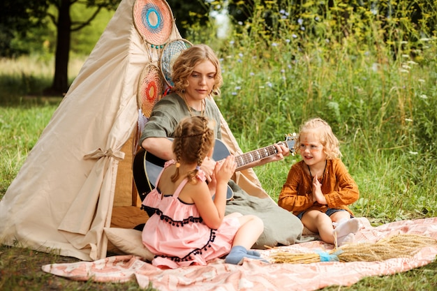 Mom plays the guitar to her children, little daughters. multicultural festival or children's party. family are sitting next to wigwam or teepee decoration. boho style decorations.