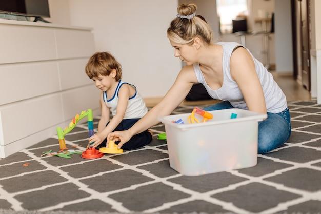 엄마는 3 세 소년과 함께 바닥에 앉아있는 동안 재생됩니다. 엄마와 아들의 관계. 디자인 기술 개발 및 훈련.
